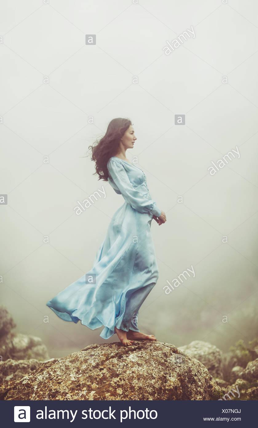 Ritratto di una metà donna adulta in piedi sulle rocce nella nebbia Immagini Stock