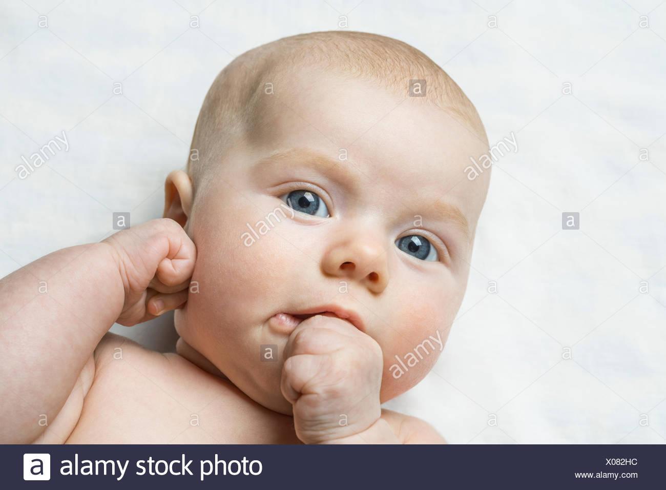 Ritratto di bambina (6-11 mesi) succhiare il pollice Immagini Stock