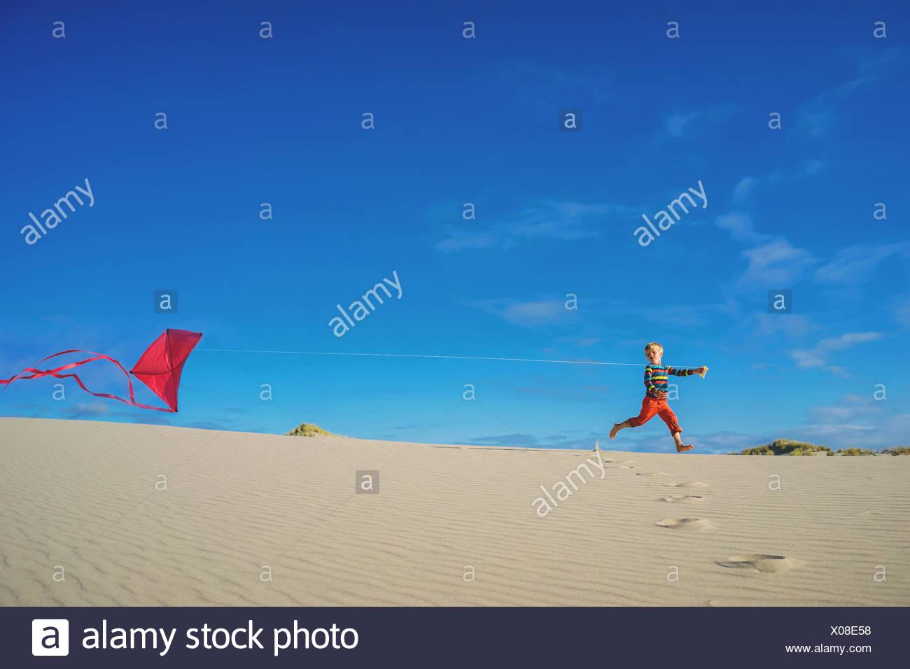 Ragazzo battenti aquilone rosso sulla spiaggia sabbiosa Immagini Stock