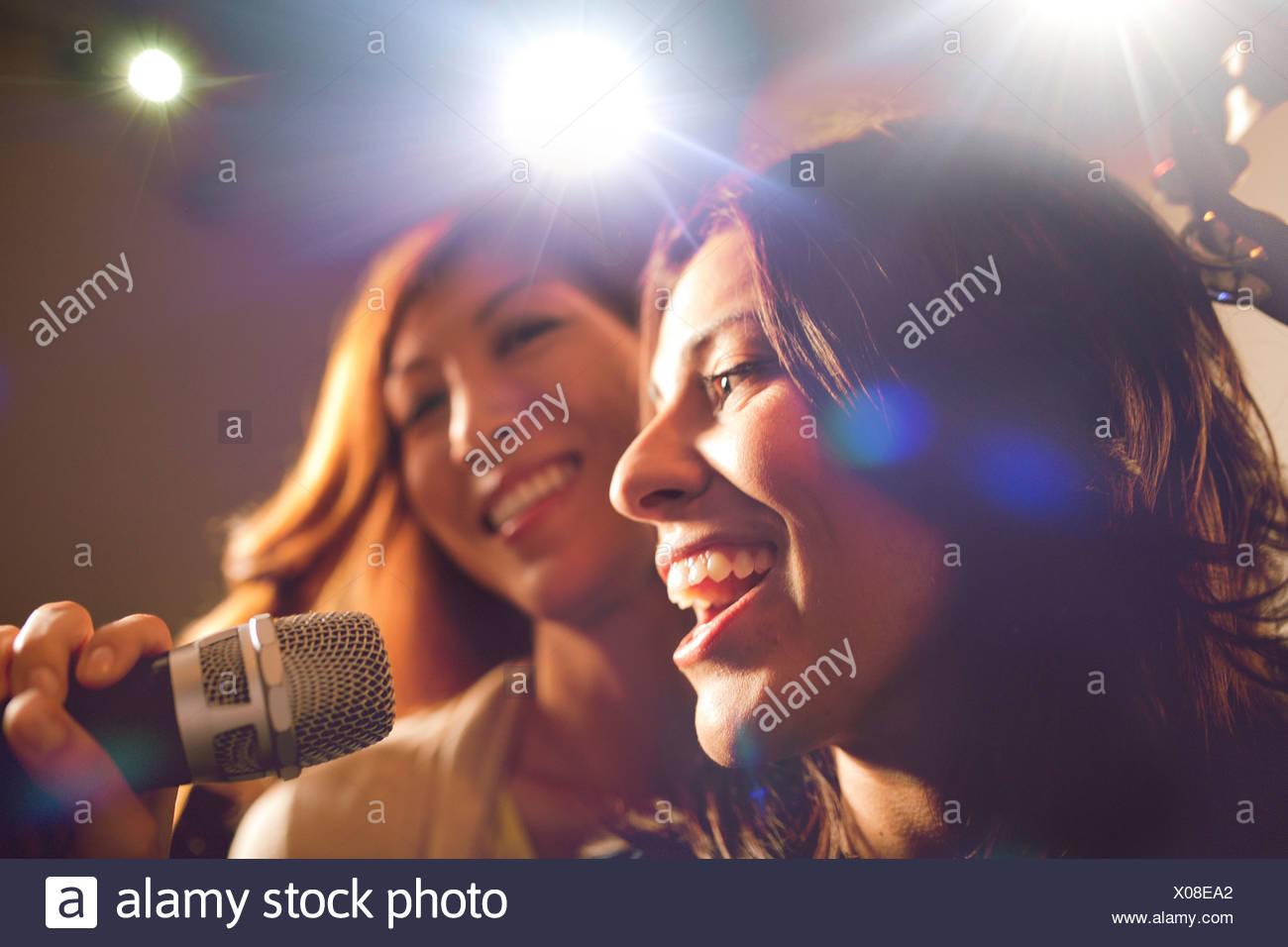 Due donne che cantano il karaoke. Immagini Stock