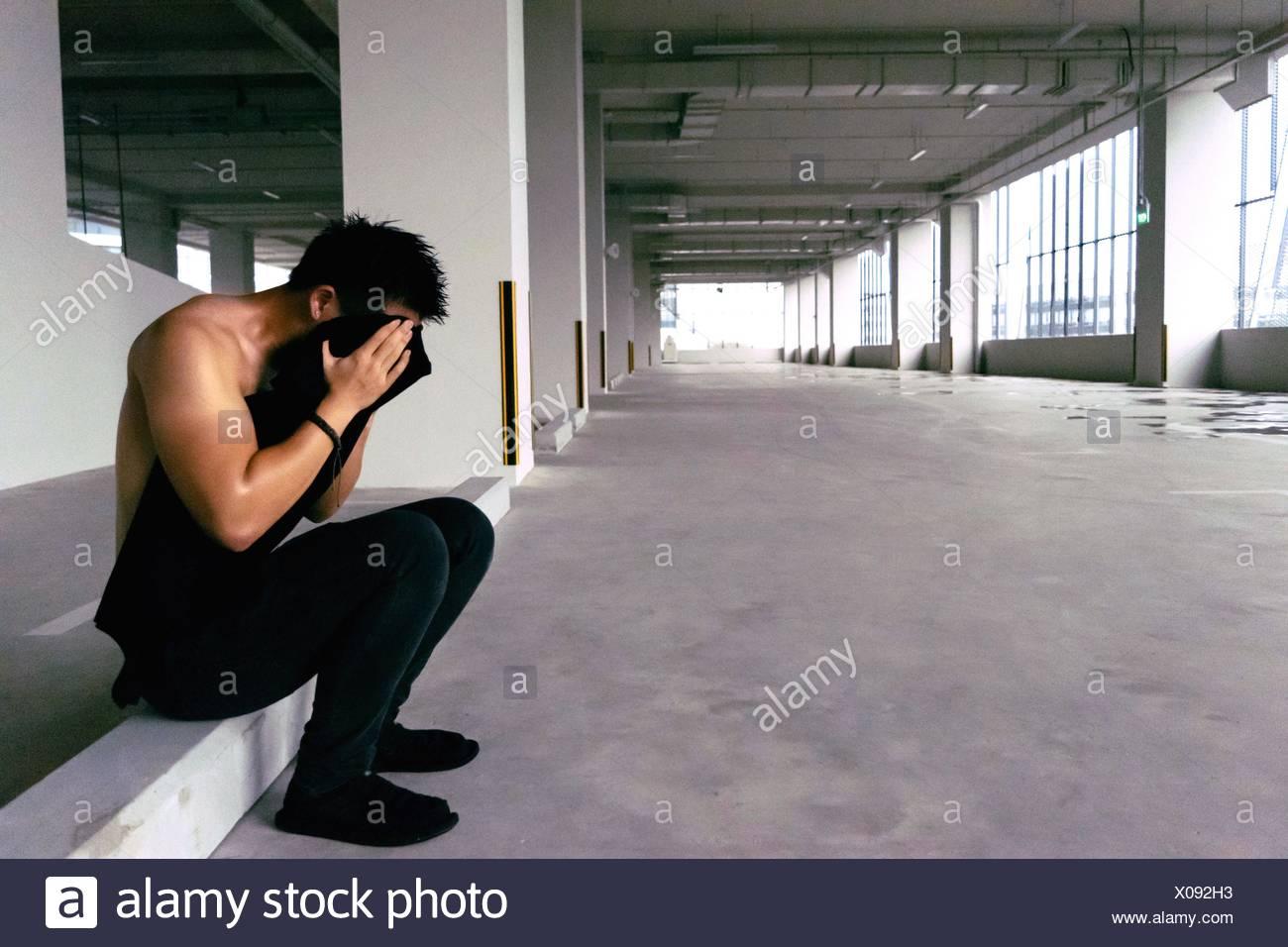 Vista laterale dell'uomo che copre la sua faccia con T-Shirt Immagini Stock