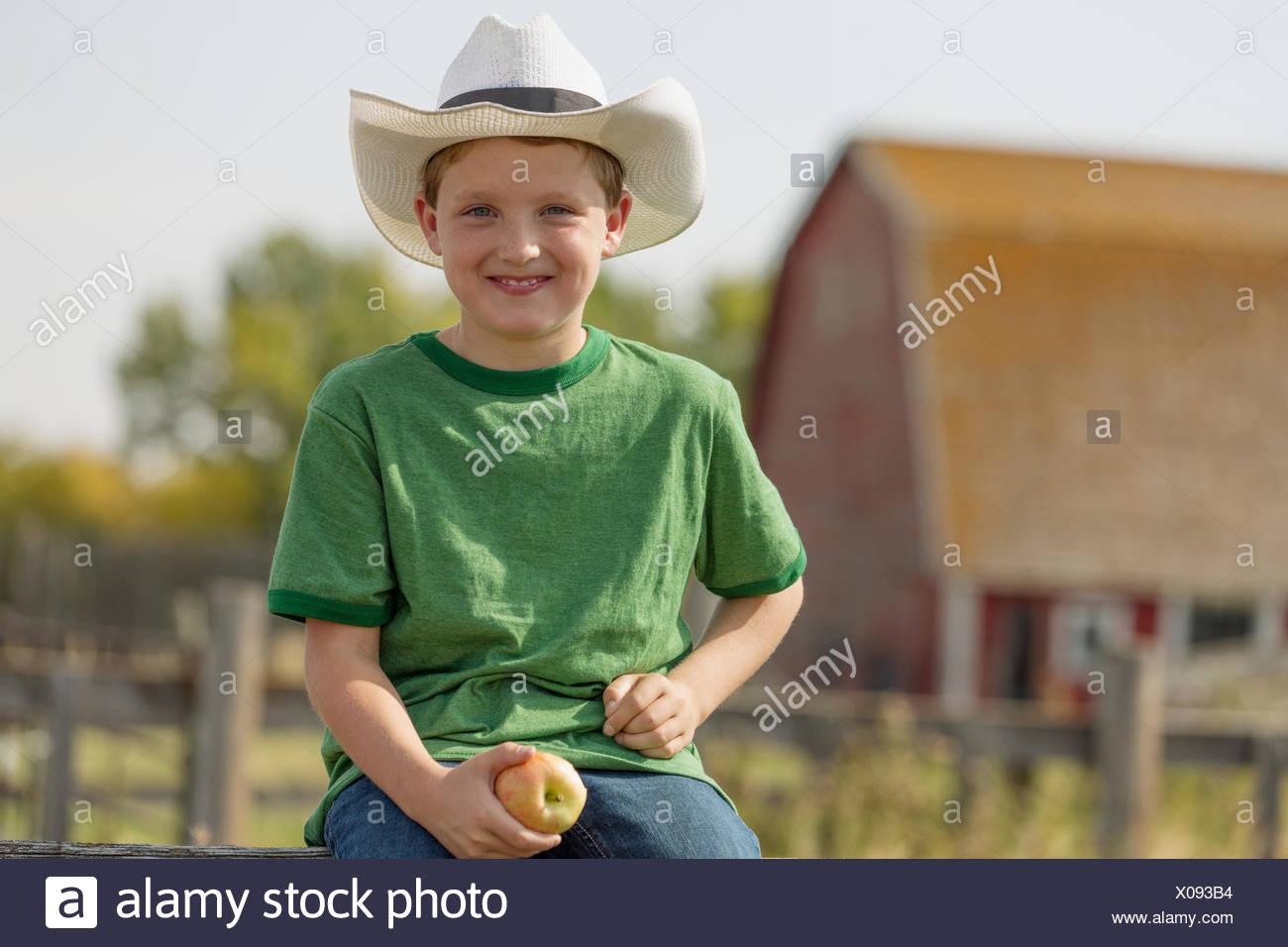 Ragazzo con il cappello da cowboy seduto sulla recinzione. Immagini Stock 55ebda9770f3