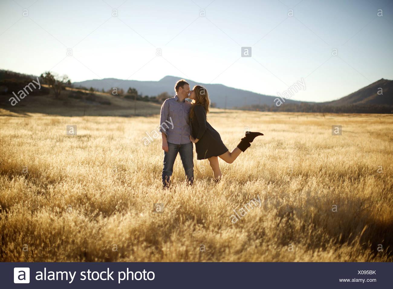 Femmina Maschio si avvicina per un bacio in un campo aperto. Immagini Stock