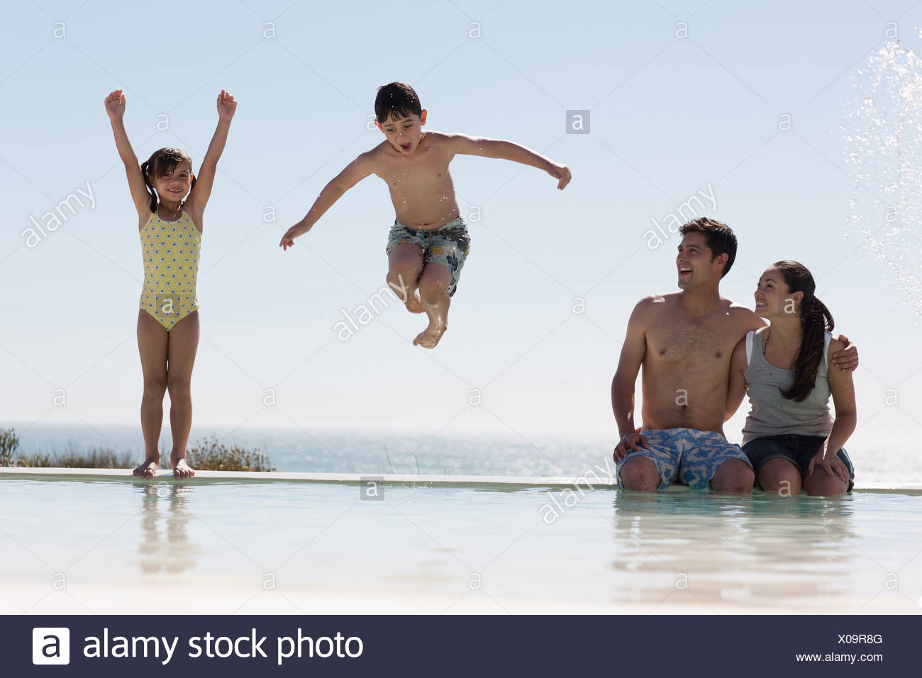 La famiglia a giocare in piscina Immagini Stock