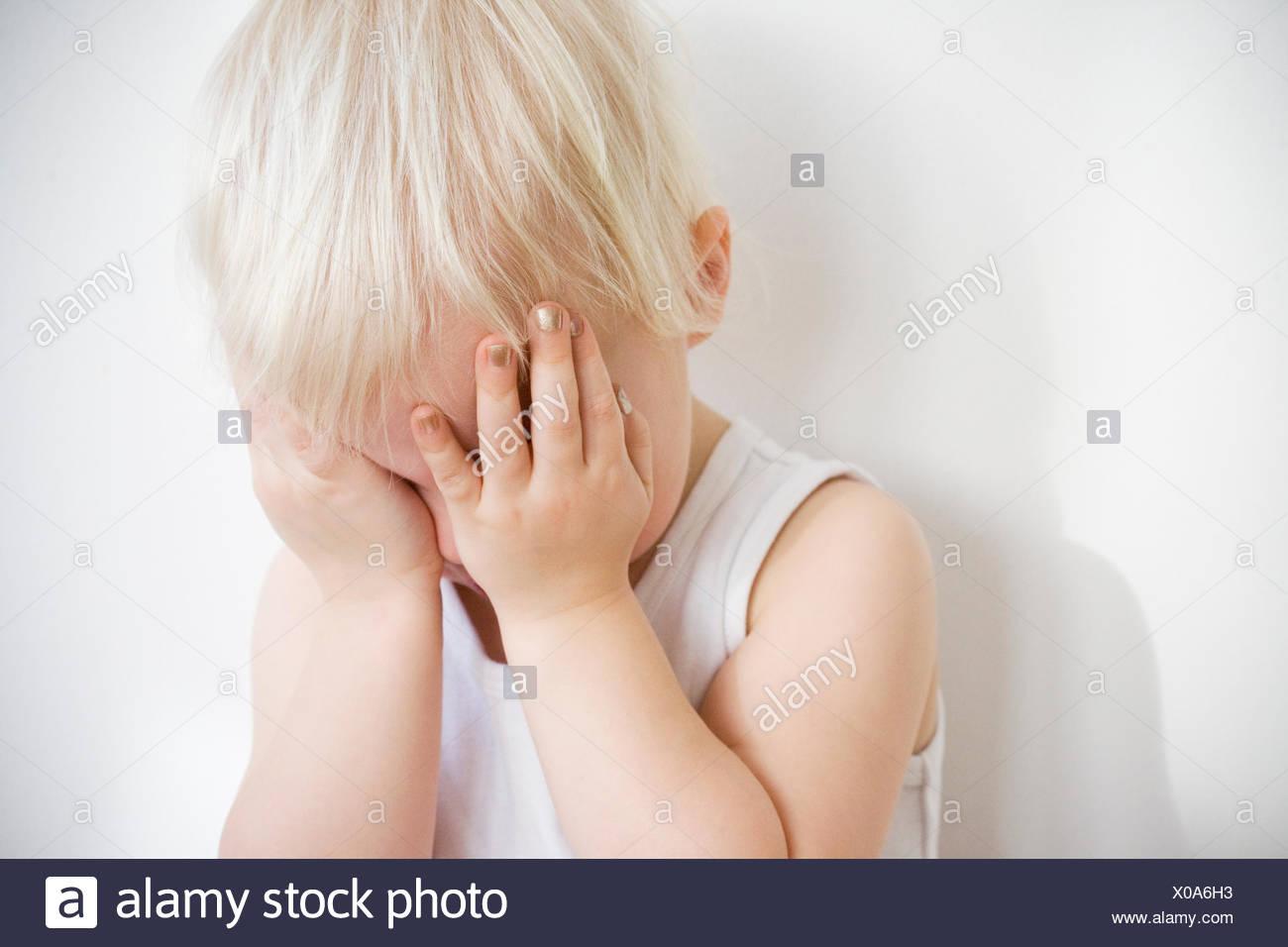 Un bambino biondo contro bianco, Svezia. Immagini Stock