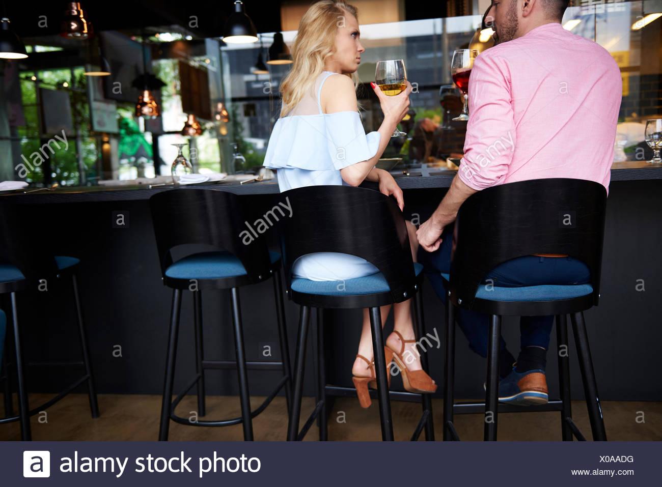 Vista posteriore dell'uomo toccando arrabbiato giovane donna del ginocchio presso il bar Immagini Stock