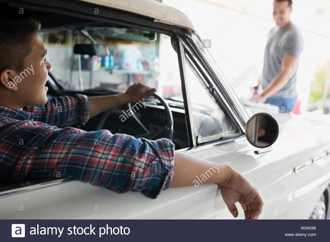 Padre e Figlio con vintage auto in garage Immagini Stock