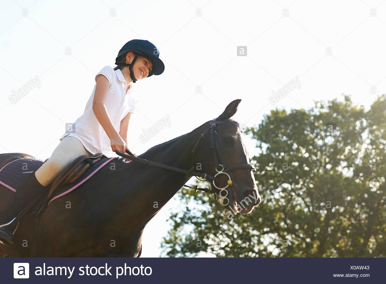 Basso angolo vista della ragazza di equitazione in campagna Immagini Stock