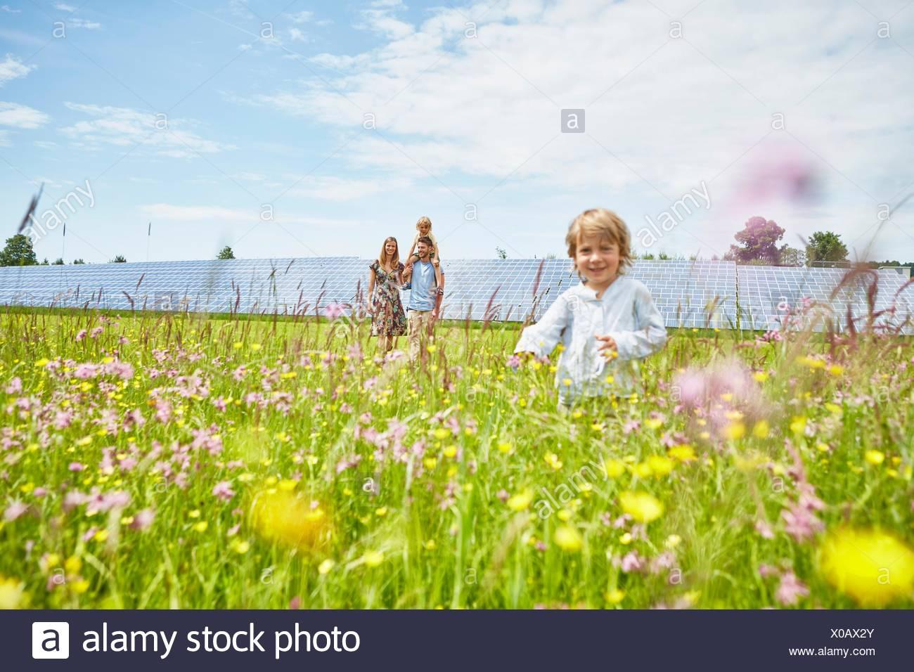 Giovane ragazzo in esecuzione attraverso il campo, madre, padre e fratello in seguito dietro, accanto alla fattoria solare Immagini Stock