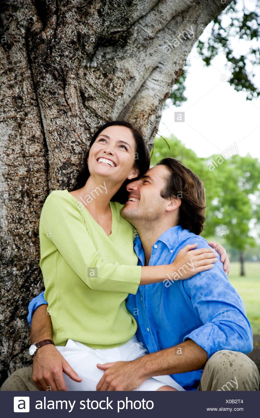 Giovane abbracciando nella parte anteriore della struttura ad albero Immagini Stock