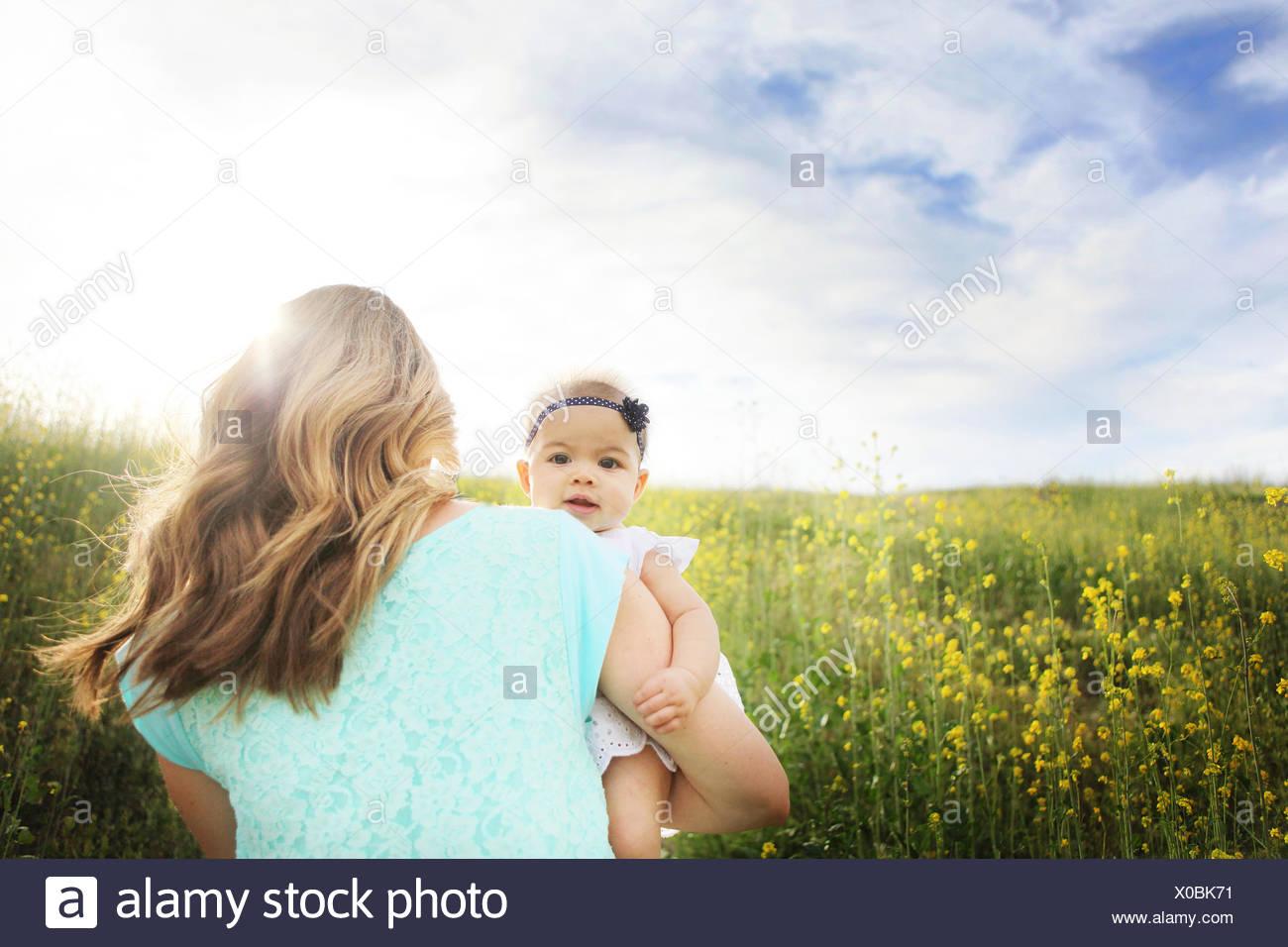Vista posteriore della donna che cammina in campo e tenendo la sua bambina Immagini Stock