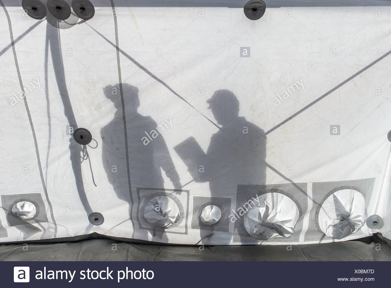 Silhouette di un team di risposta alle emergenze dei lavoratori all'interno di centro di controllo tenda Immagini Stock