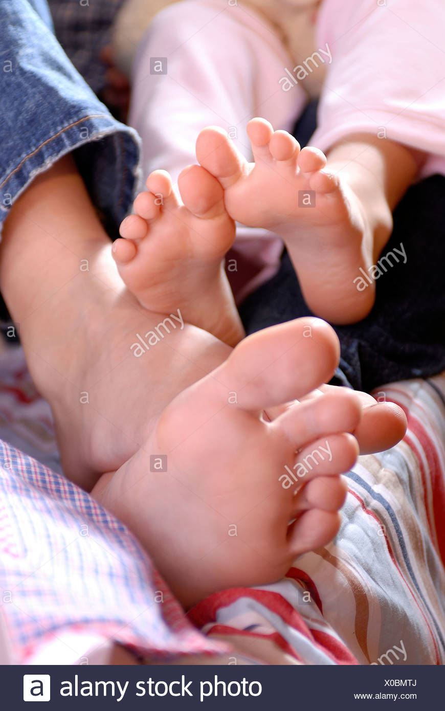 Piccoli e grandi piedi nel letto, scalzi, coccole, bambini nel letto Immagini Stock