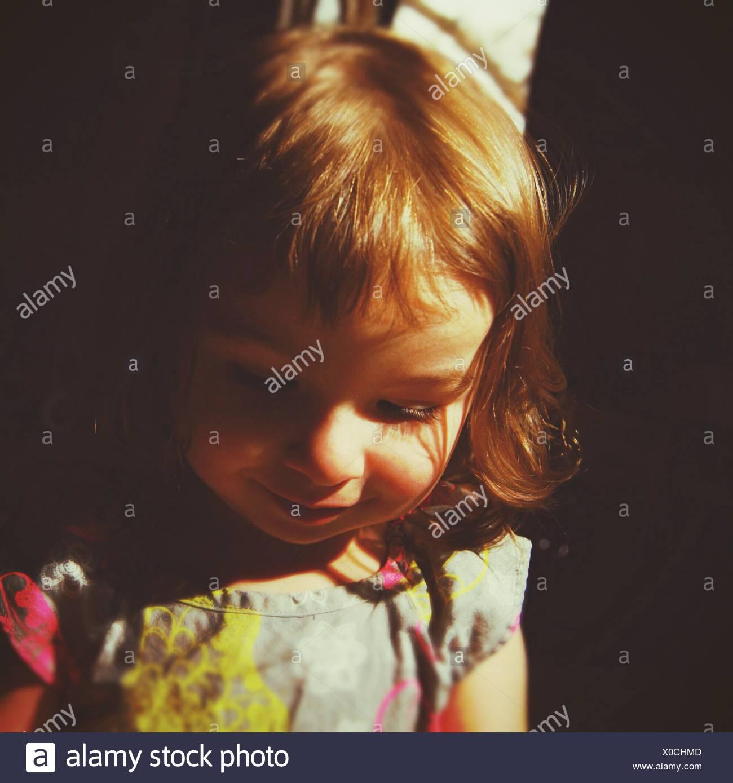 Close-Up di Carino ragazza sorridente mentre guardando verso il basso Immagini Stock