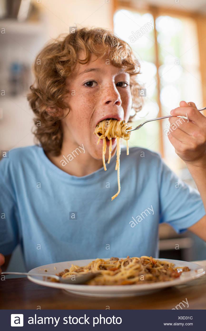 Ragazzo adolescente mangiare spaghetti al tavolo da pranzo Immagini Stock