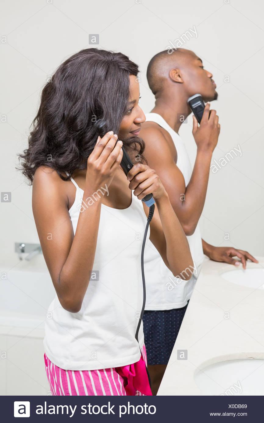 Giovane uomo la rasatura e la giovane donna capelli dritti Immagini Stock