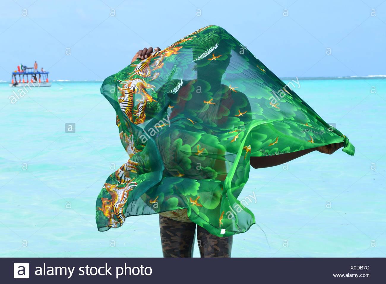 Donna che mantiene Sarong in spiaggia Immagini Stock