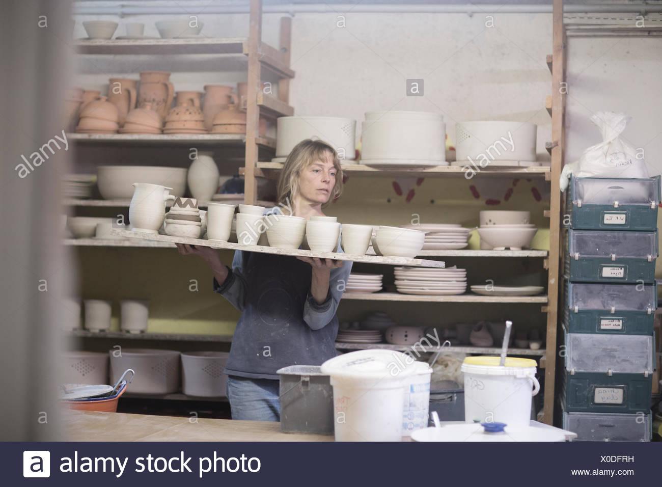 Potter femmina che porta il vassoio di vasi di terracotta in officina Foto Stock