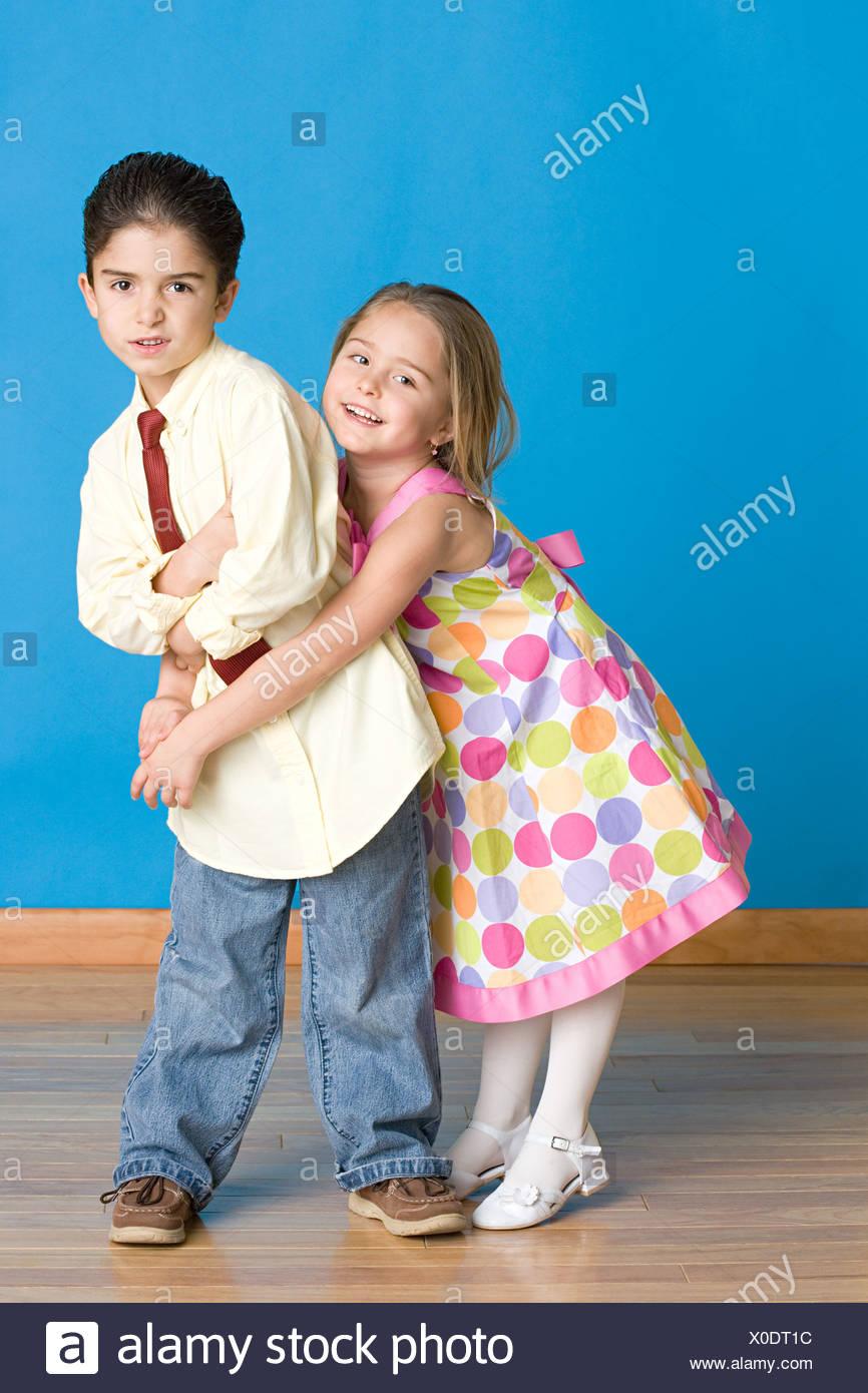 Ragazza cercando di abbraccio boy Immagini Stock