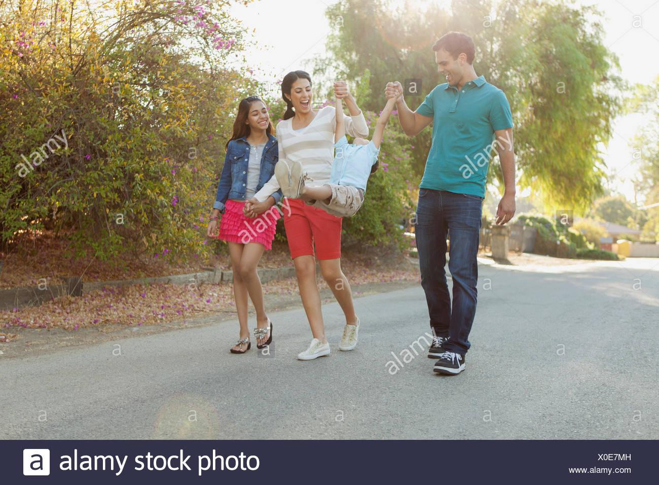 I genitori swinging giovane figlio mentre sono fuori per una passeggiata Immagini Stock