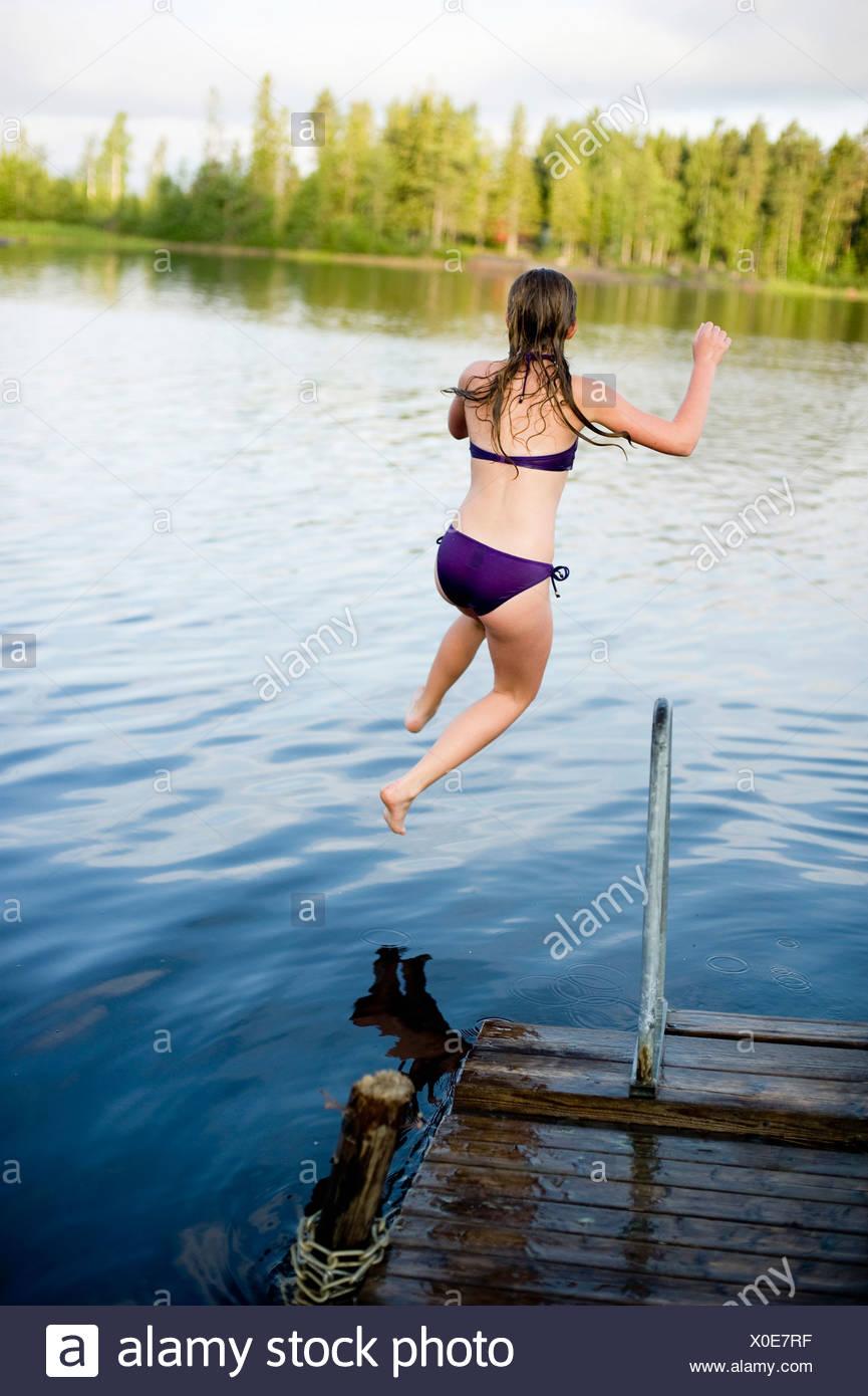 Primo piano sulla ragazza saltando in acqua Immagini Stock