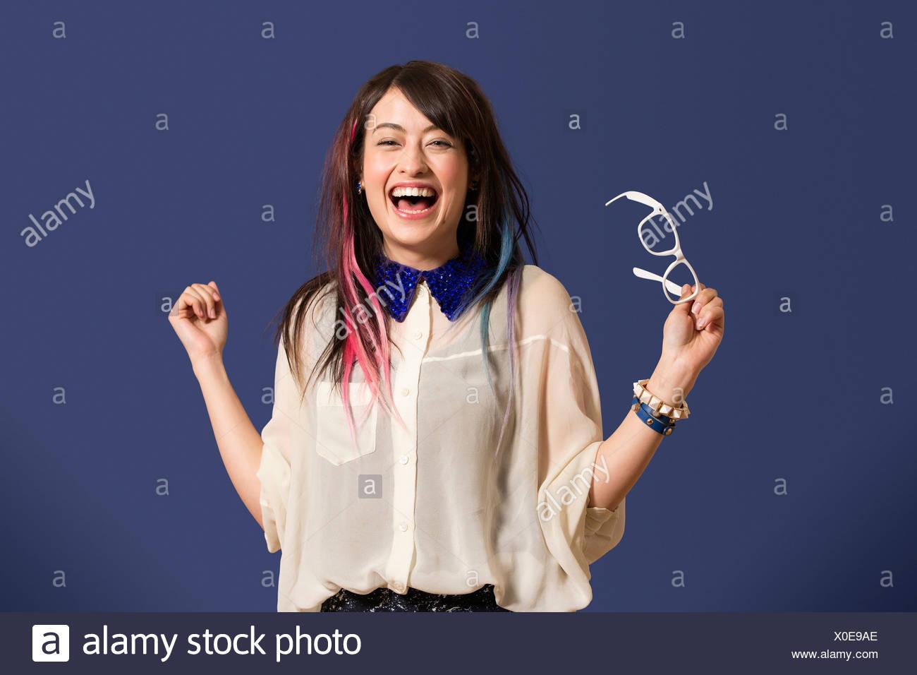 Ritratto di giovane donna con capelli tinti azienda bicchieri Immagini Stock