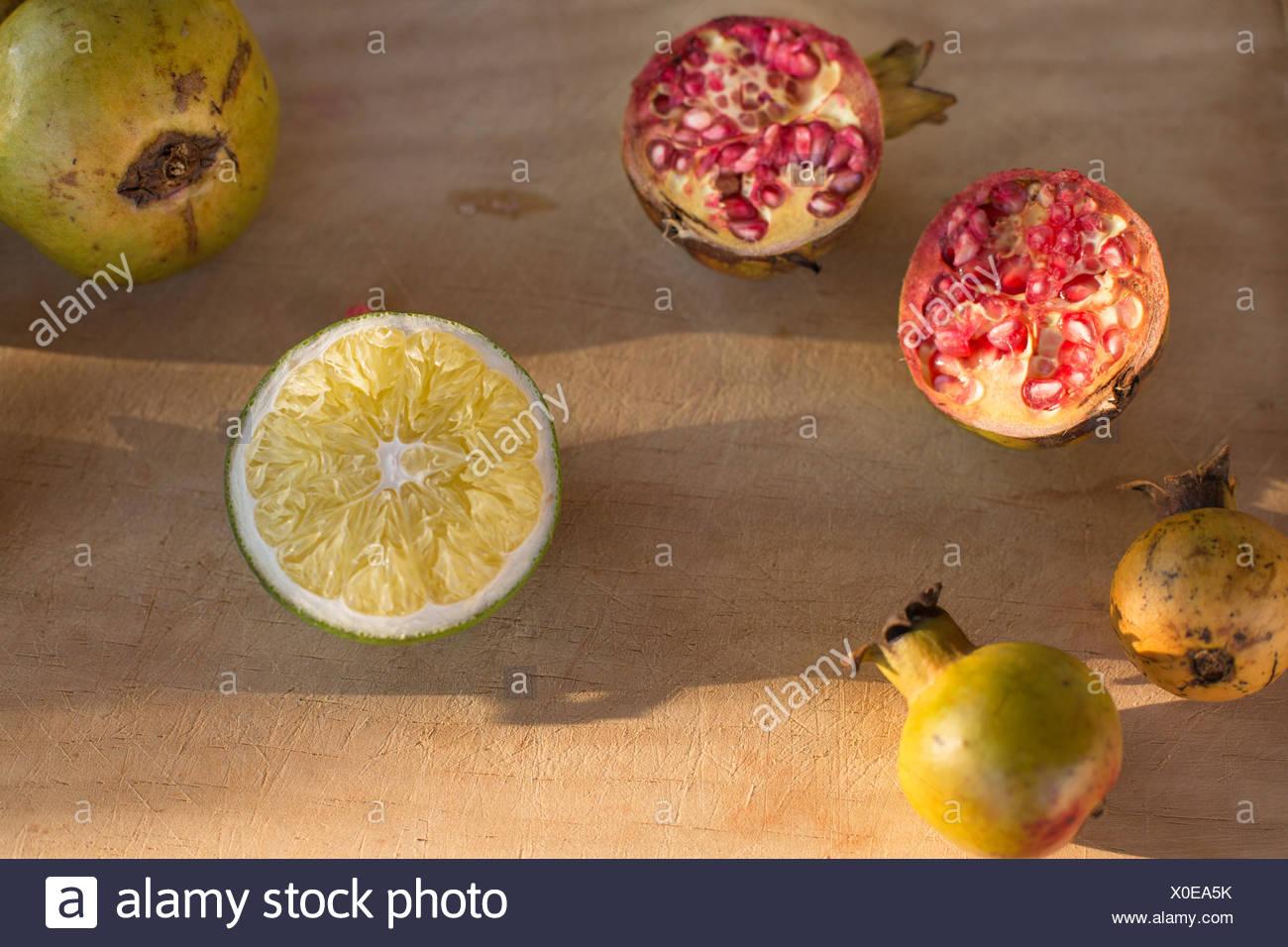 Tagliare i melograni nel tardo pomeriggio di sole con limone pallido contro uno sfondo di legno Immagini Stock