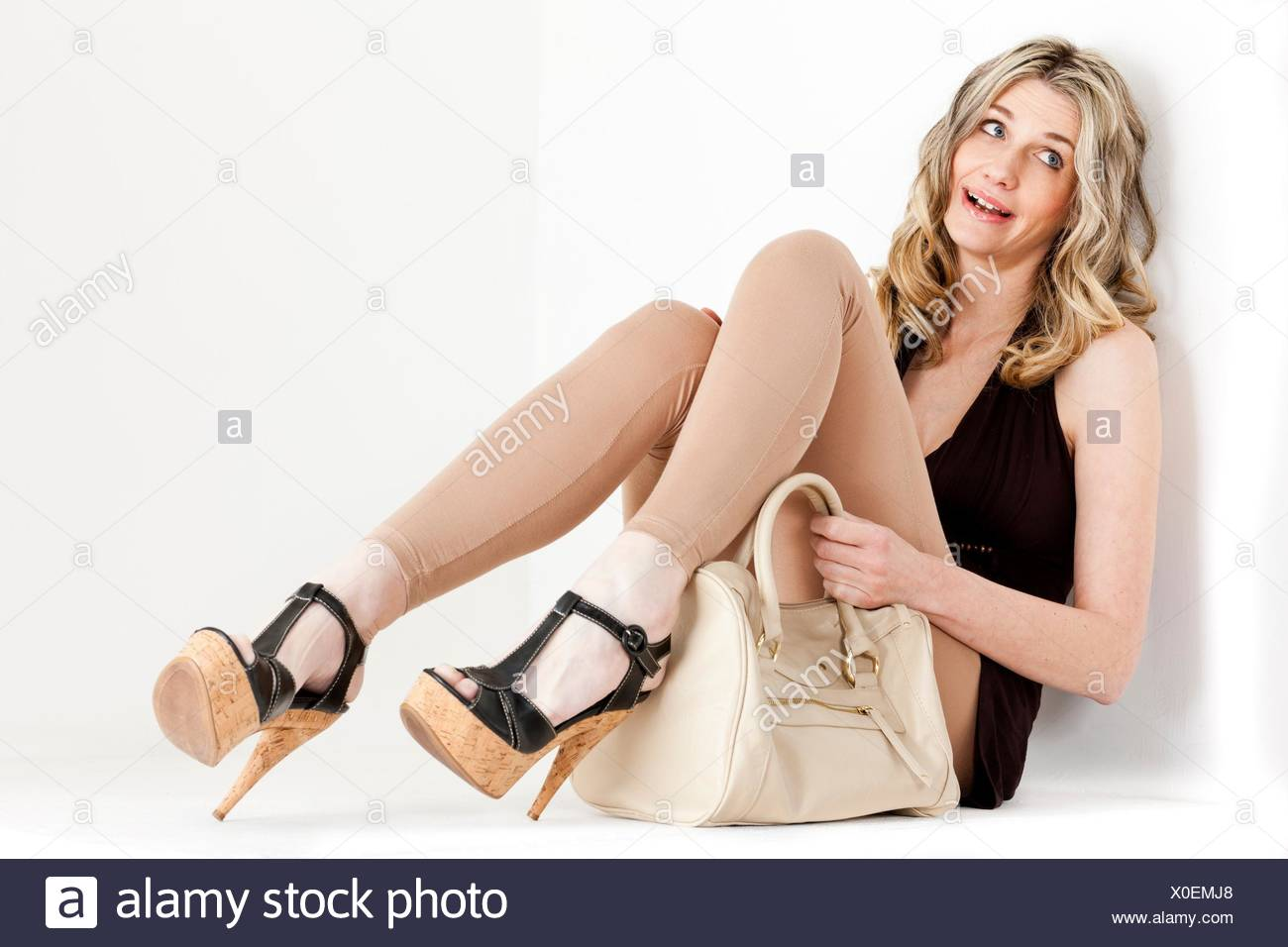 23476710b73e Donna seduta indossando vestiti estivi e scarpe con una borsetta ...