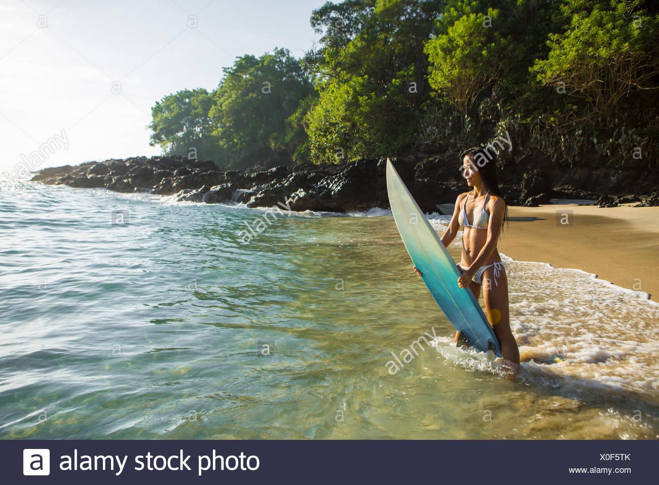 Metà donna adulta sulla spiaggia in piedi nel surf mentre tiene il suo bordo, Bali, Indonesia Immagini Stock