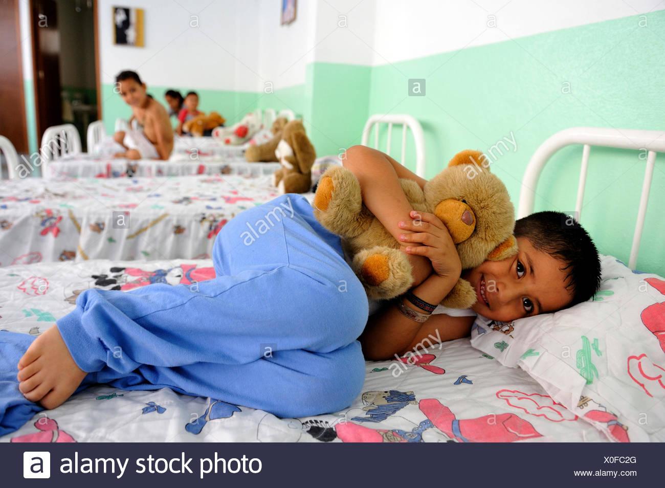 Ragazzo con un grosso orso di peluche sul suo letto nel dormitorio di un orfanotrofio, Queretaro, Messico, America del Nord e America Latina Immagini Stock