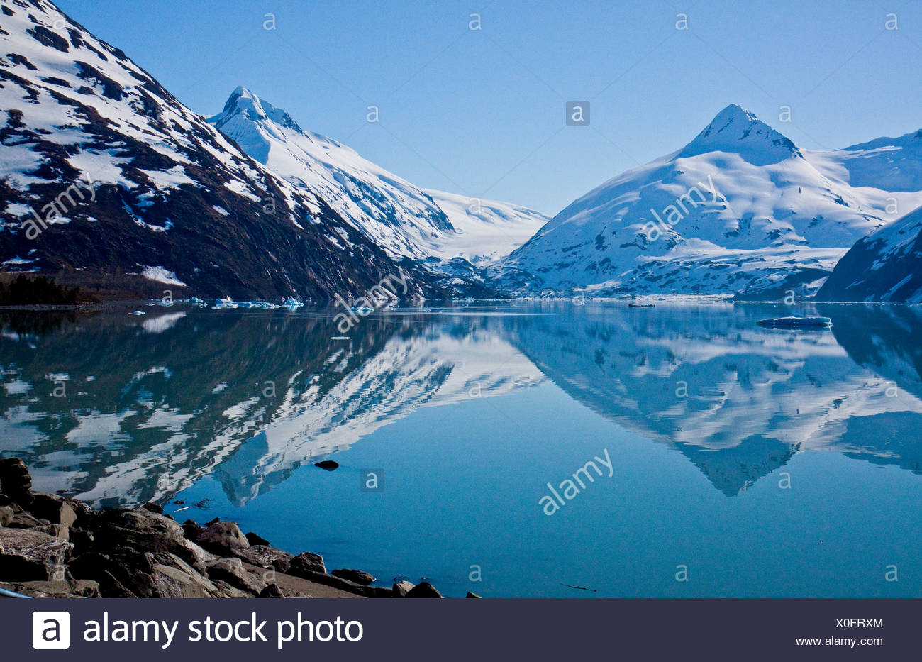 Bella riflessioni delle montagne coperte di neve nel lago di Portage Immagini Stock