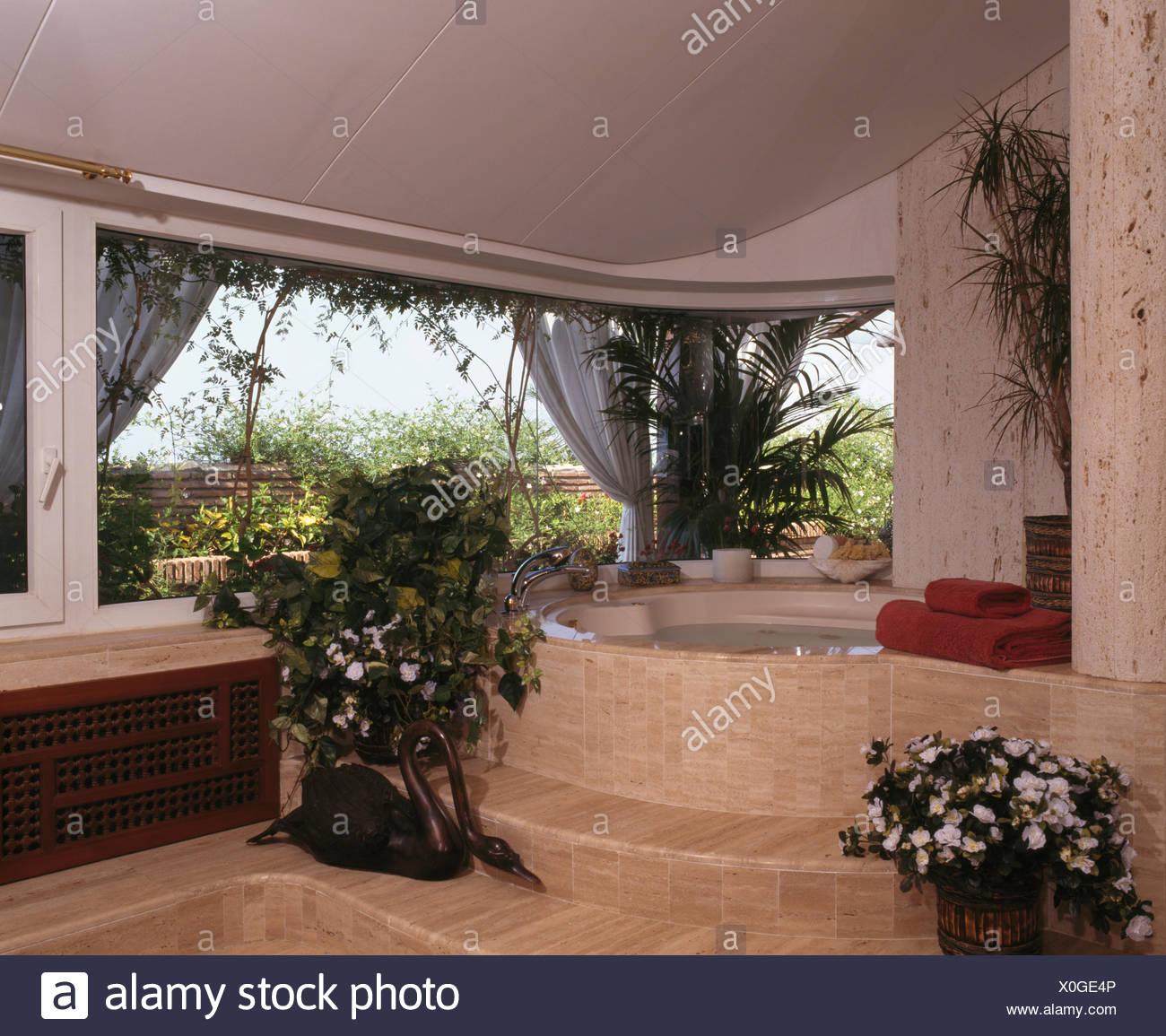 Pentole di houseplants sui passi fino alla stanza da bagno in marmo ...