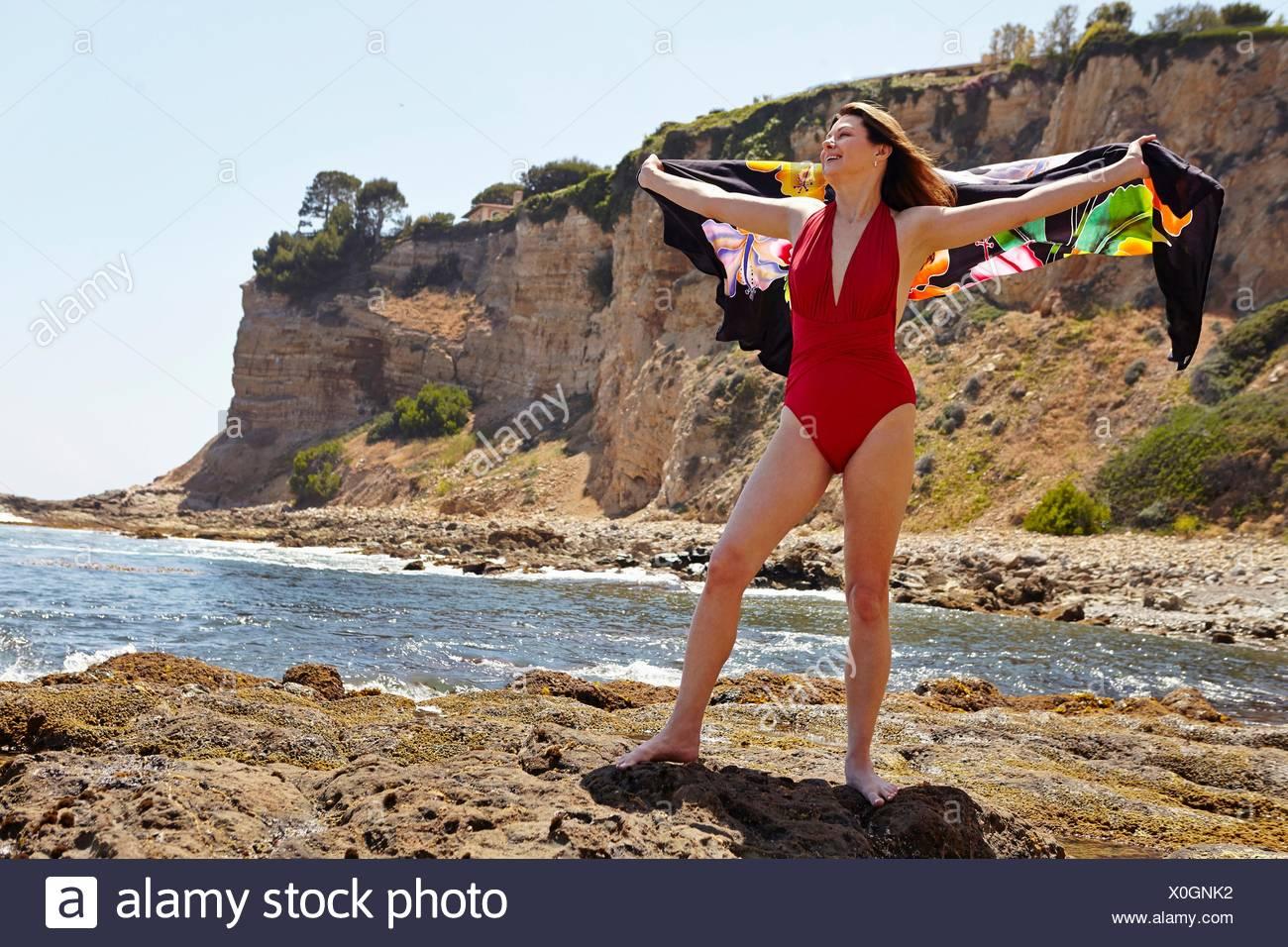 Ritratto di donna matura rosso da indossare il costume da bagno in posa con sarong a costa Immagini Stock
