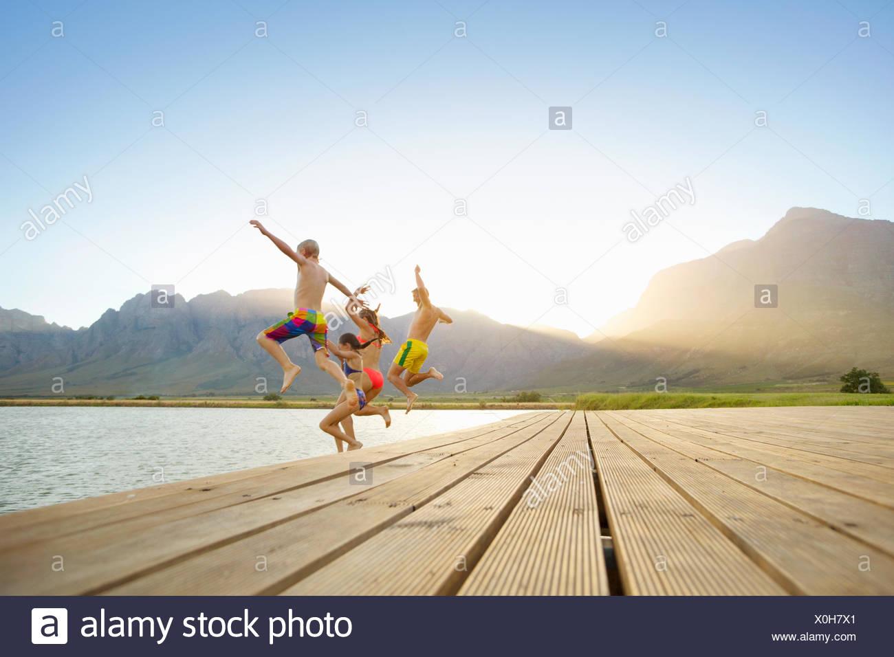 La famiglia, in costume da bagno, il salto in un lago da un pontile Immagini Stock