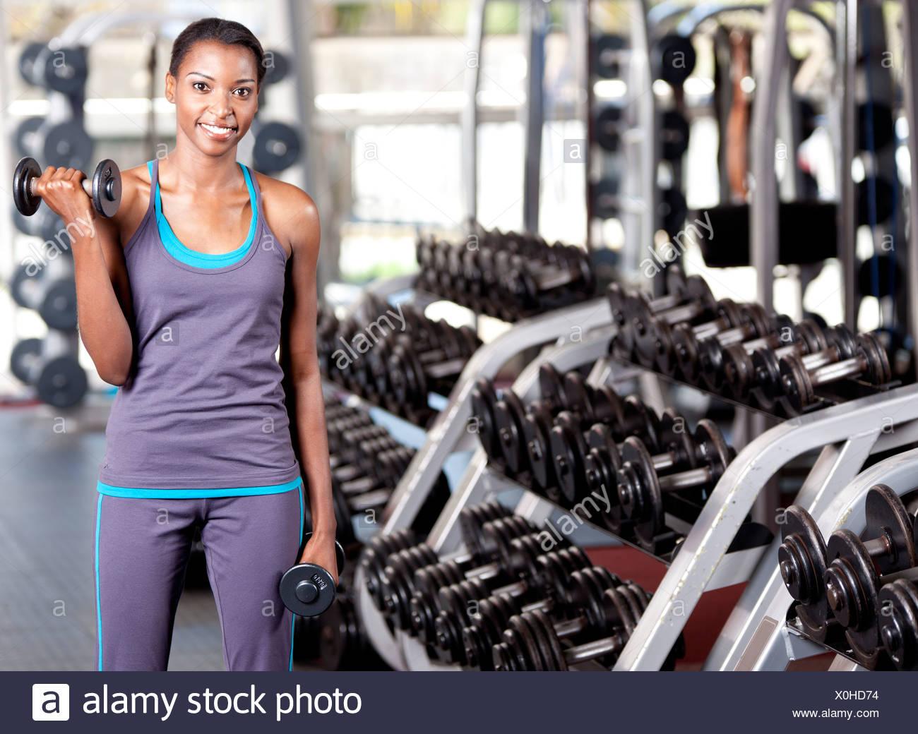 Giovane femmina nero di sollevare i pesi nella palestra Immagini Stock
