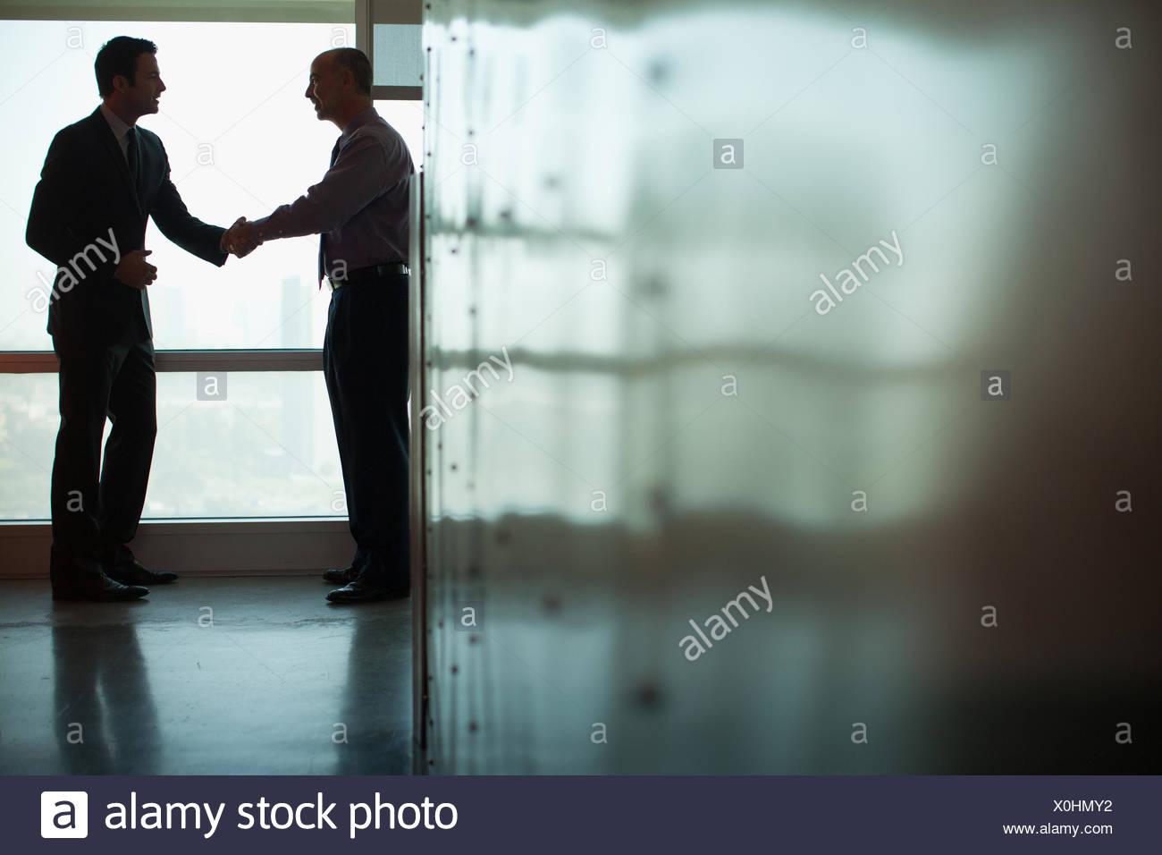 Uomini d'affari si stringono la mano in ufficio Immagini Stock