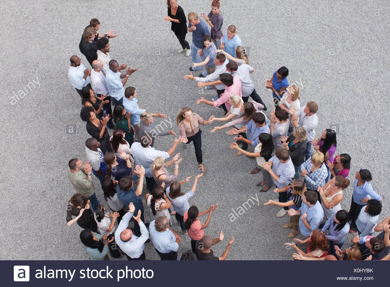 Donna oltrepassando la folla ad alta fiving persone Immagini Stock