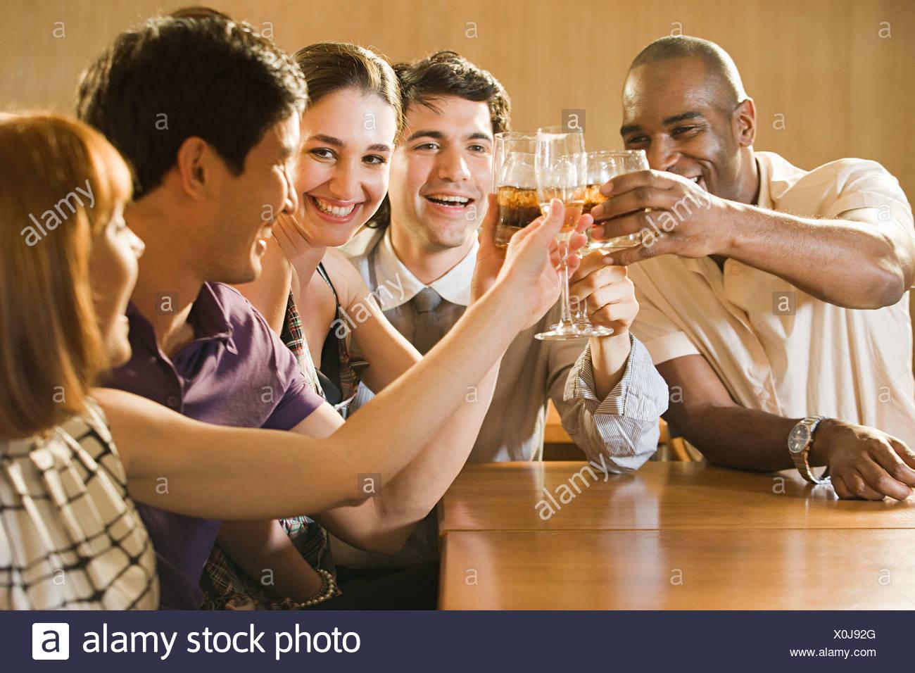 Amici a celebrare in un bar Immagini Stock