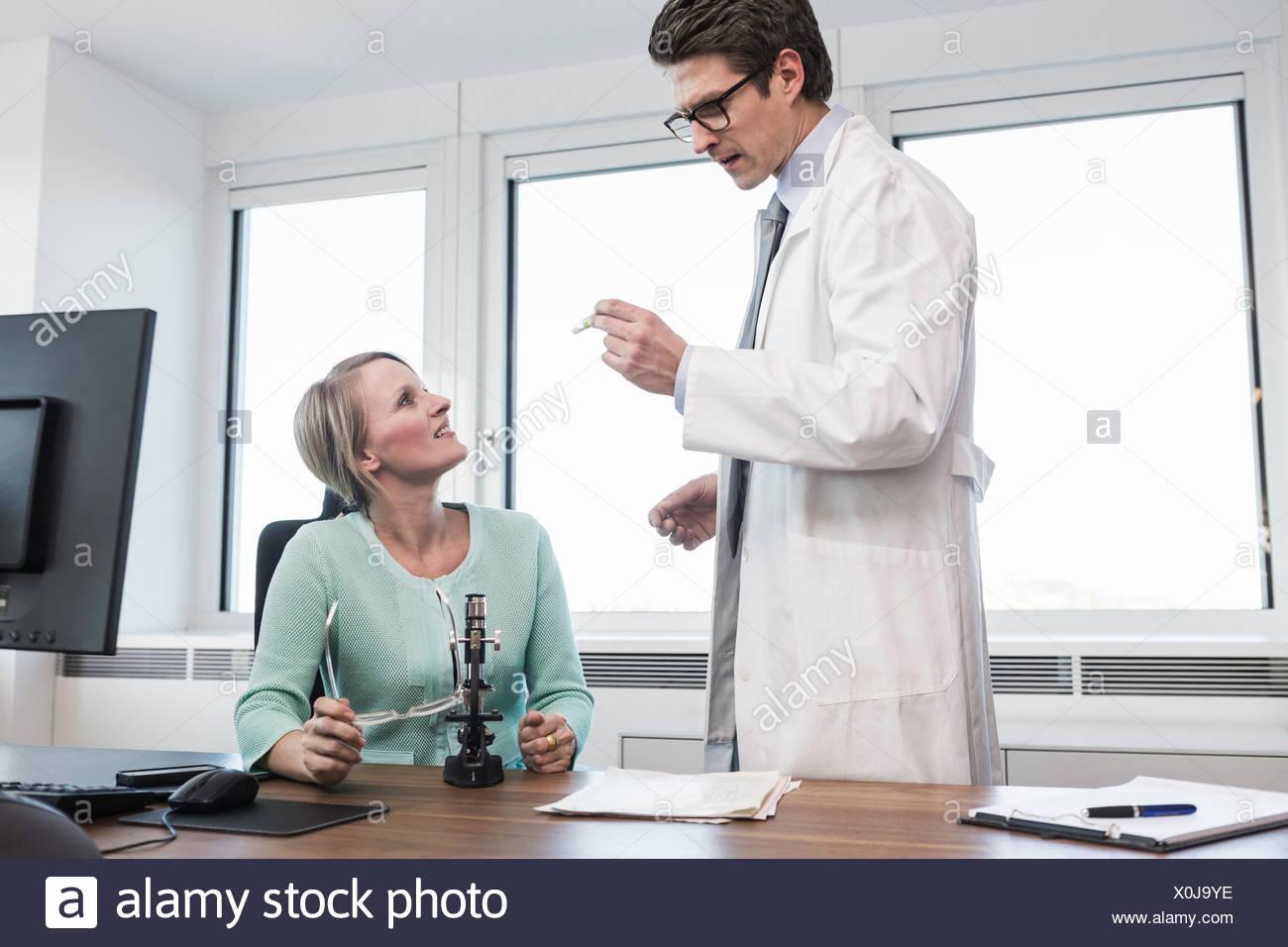 Uomo che indossa camice azienda provetta parlando di donna sat a scrivania Immagini Stock