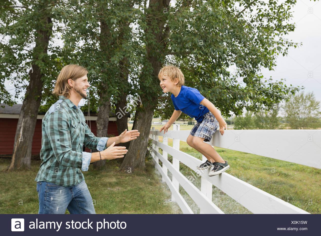 Giocoso figlio salta fuori da recinzione in bracci di padri Immagini Stock