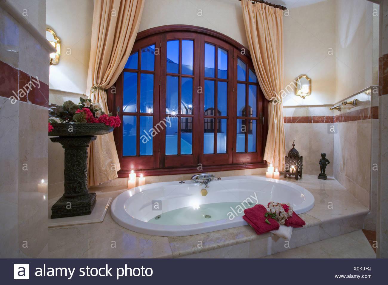 Vasca Da Bagno Sotto Finestra : Le candele accese sul rivestimento della vasca ovale sotto la grande