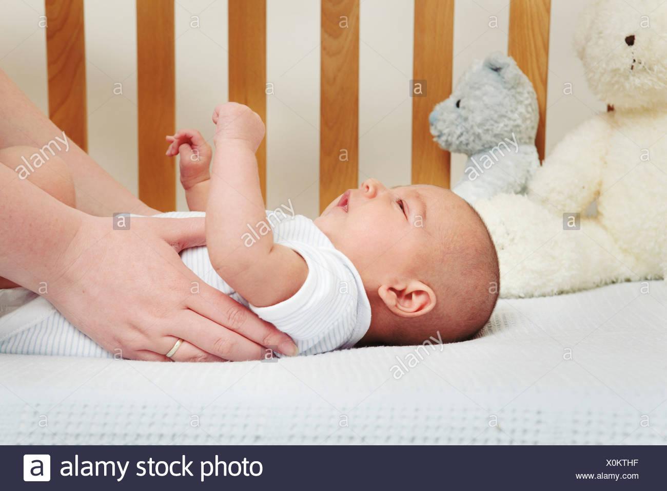 Madre di prelevare il bambino dal presepe Immagini Stock