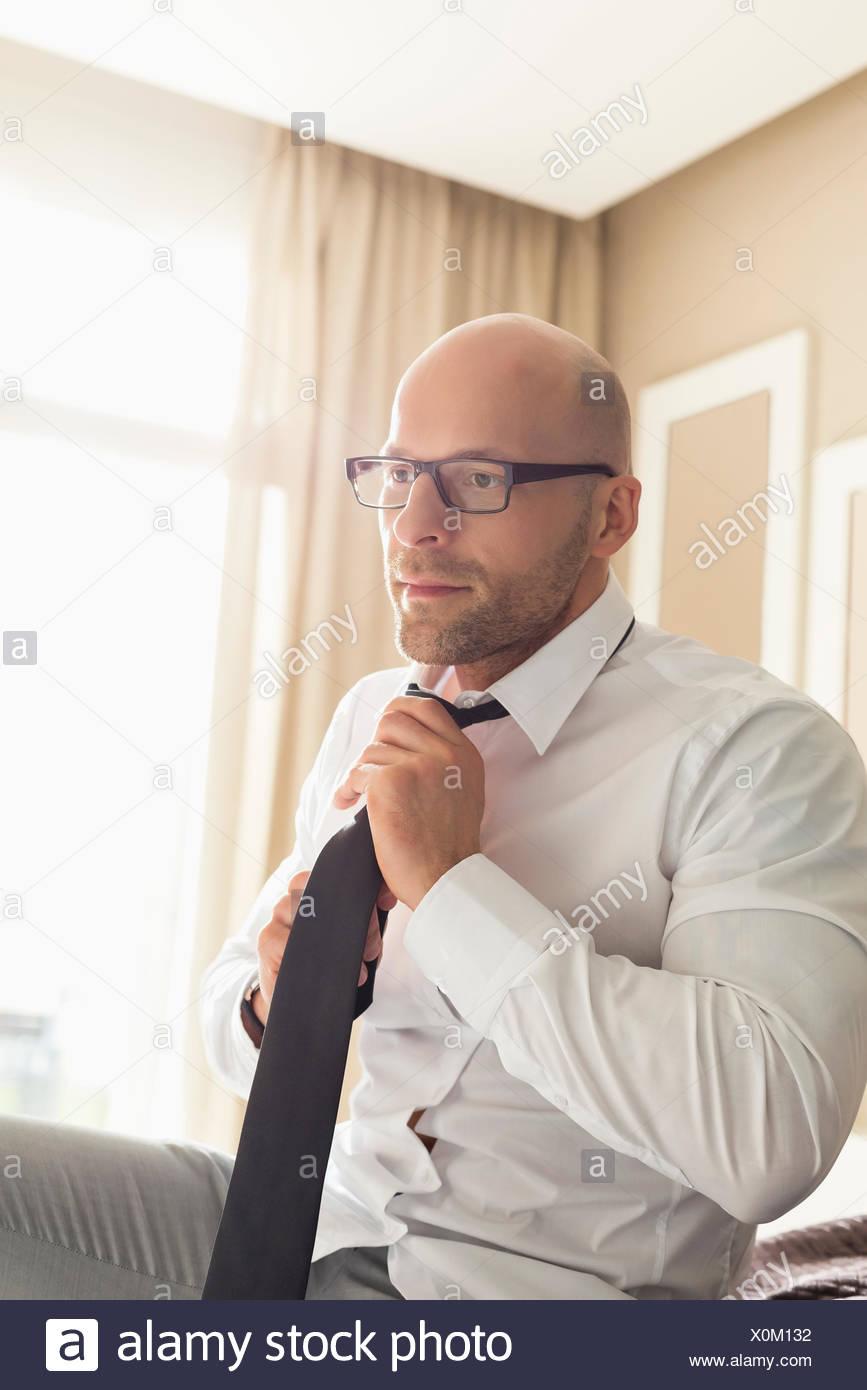 Adulto medio imprenditore cravatta di regolazione a casa Immagini Stock