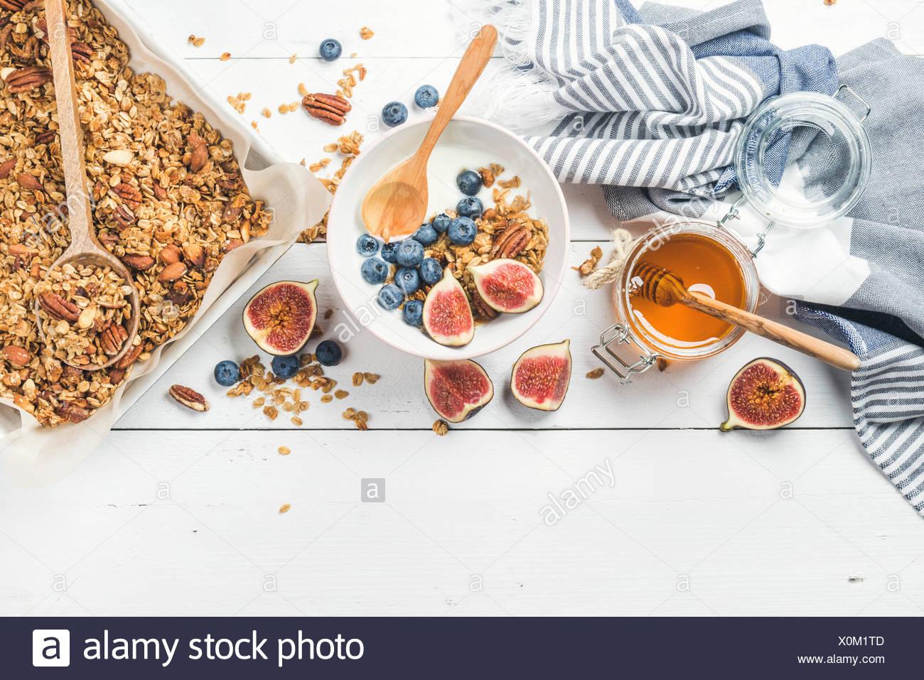 Sana colazione set. Oat granola con dadi, yogurt, miele, fichi freschi e mirtilli nella ciotola sul bianco sullo sfondo di legno, parte superiore Immagini Stock