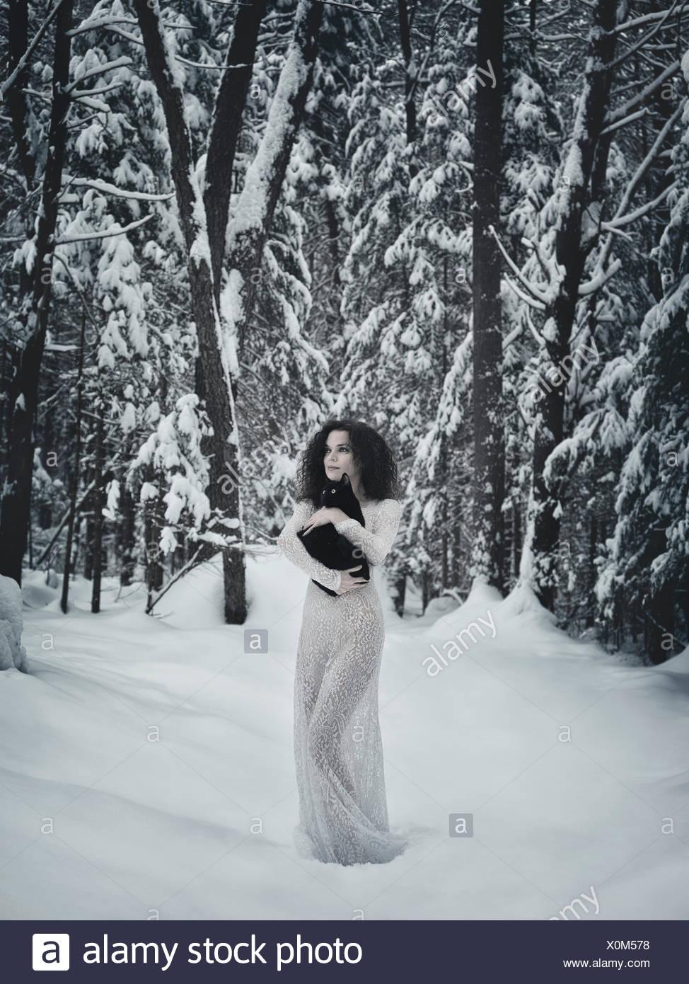 Bella donna in bianco abito lungo passeggiate nella neve con un gatto nero nelle sue mani, inverno, schnee, wald Immagini Stock
