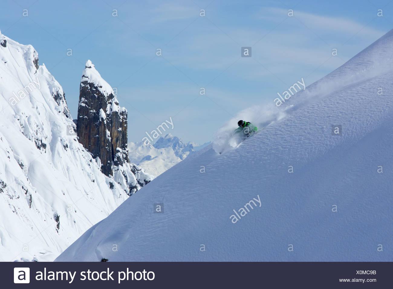 Sciatore facendo un giro stretto sulla neve intatta Immagini Stock