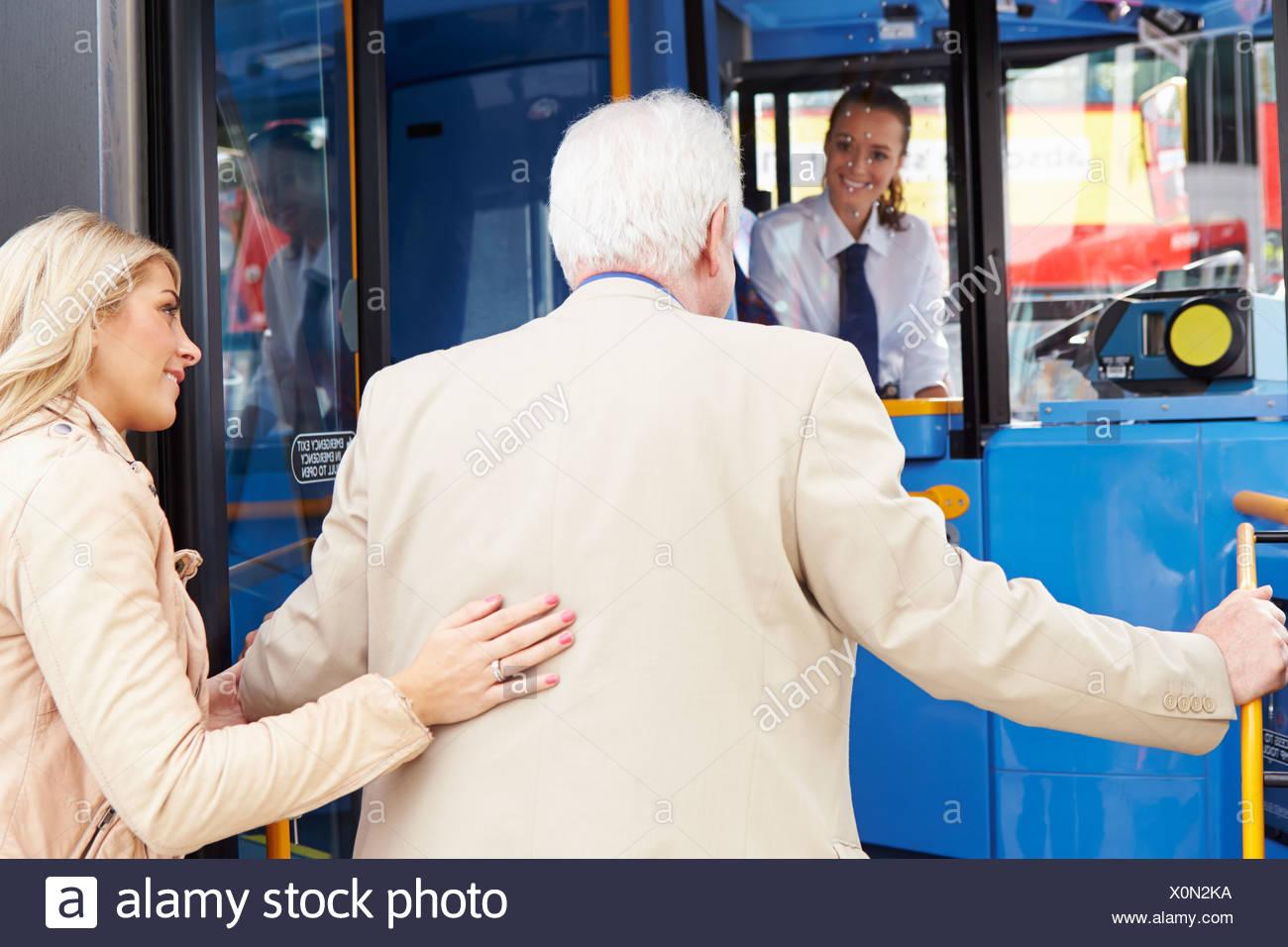 Donna Senior aiuta l uomo a bordo dei bus Immagini Stock