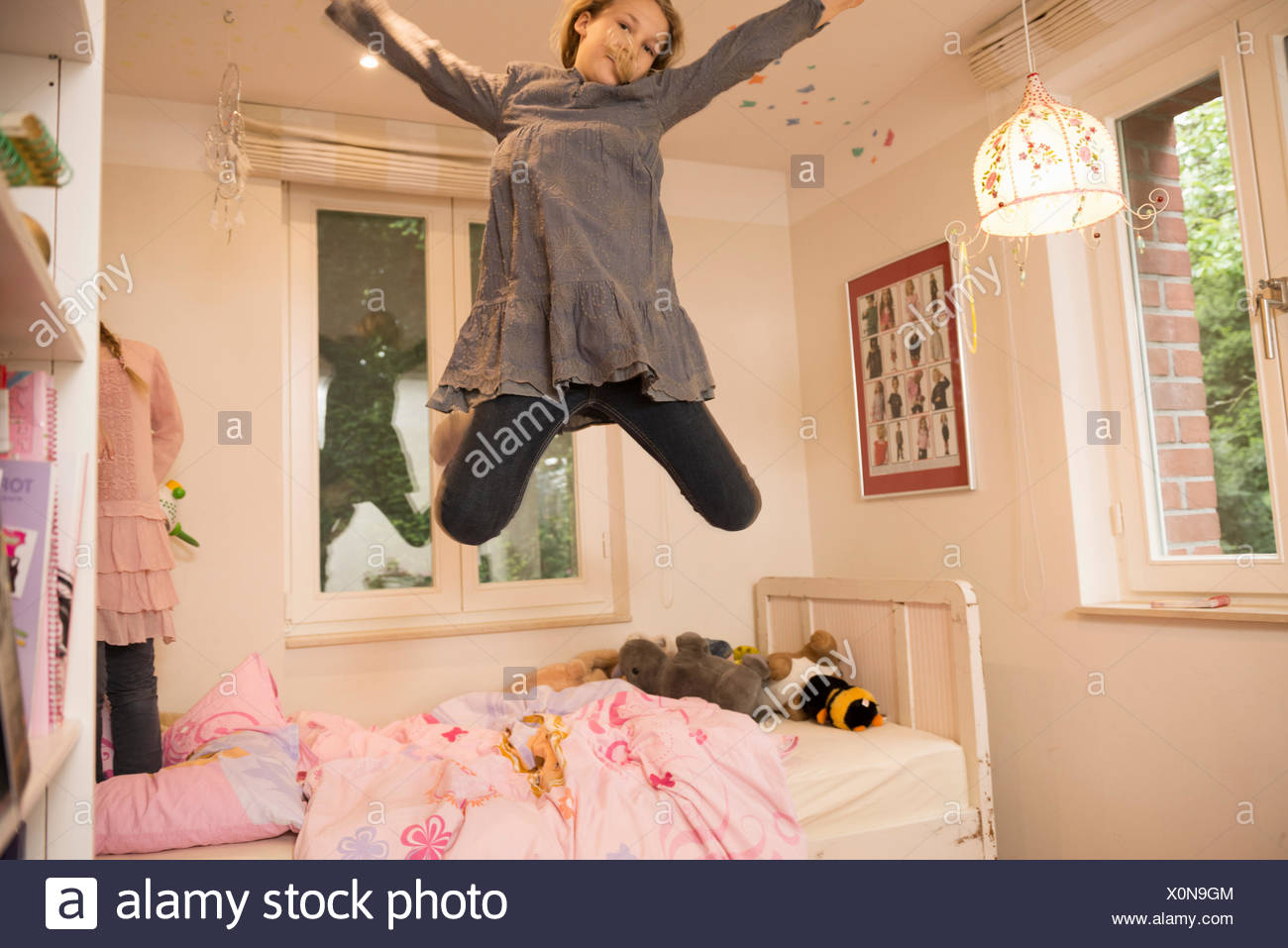 Ragazza jumping metà aria dal letto in camera da letto Immagini Stock