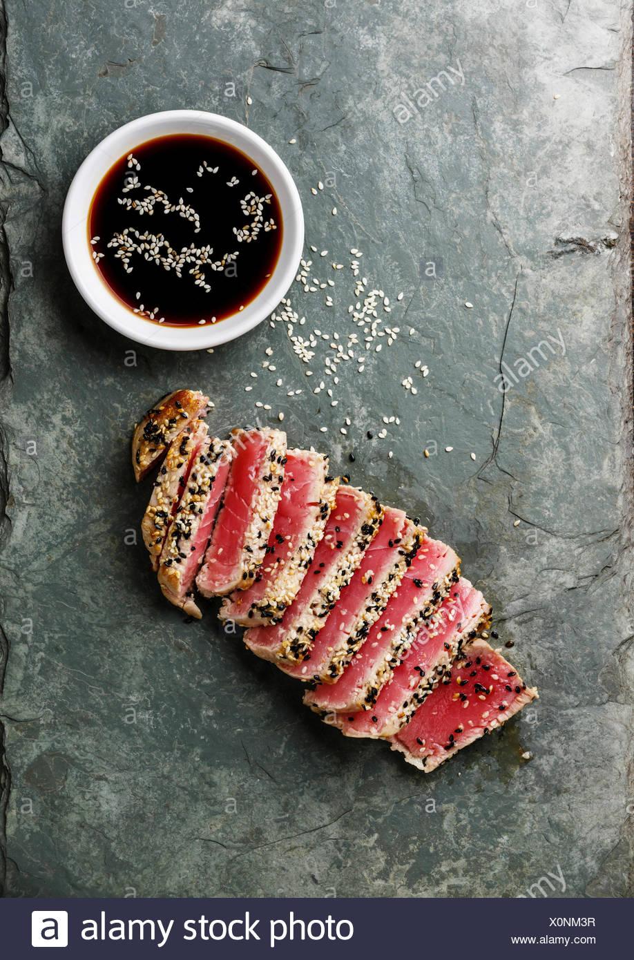 Fette di tonno grigliato bistecca con sesamo e salsa di soia su pietra ardesia board Immagini Stock