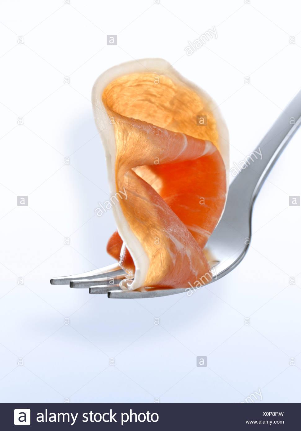 Fetta di prosciutto crudo su una forcella Immagini Stock